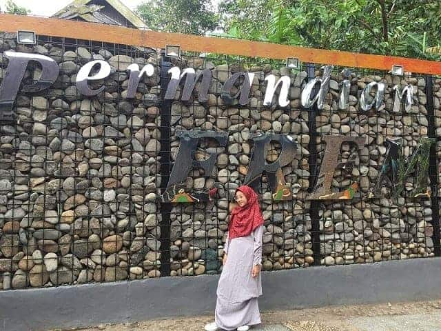 Naura, mahasiswi Akuntansi UNIFA berpose di depan dinding batuan Nama Permandian Eremerasa